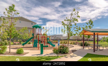 Panorama Park at a sunny neighborhood with childrens playground and pavilion eating area - Stock Photo