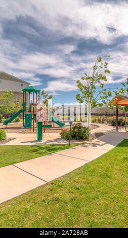 Vertical frame Park at a sunny neighborhood with childrens playground and pavilion eating area - Stock Photo