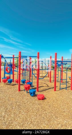 Vertical frame Park with vivid childrens playground and pavilion picnic area overlooking lake - Stock Photo