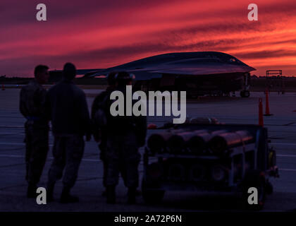 Maintainers assigned to Whiteman AFB's 509th and 131st Bomb Wings watch a  sunset near a B-2 Spirit Stealth Bomber, Oct 24, 2019. Routine training prepares  Airmen to execute global strike missions anytime, anywhere. (U.S. Air Force photo by Senior Airman Thomas Barley) - Stock Photo