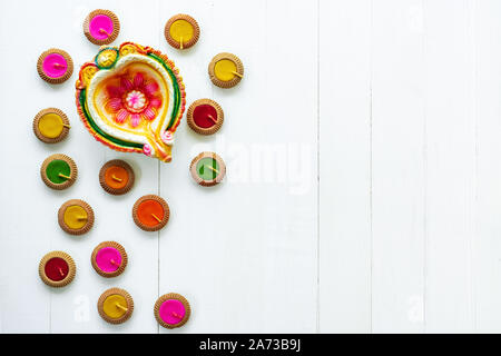 Happy Diwali - Clay Diya lamps lit during Dipavali, Hindu festival of lights celebration. Colorful traditional oil lamp diya on white wooden backgroun - Stock Photo