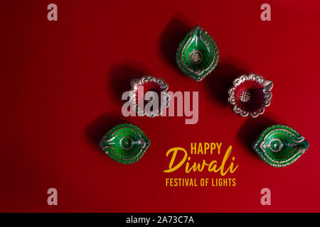 Happy Diwali - Clay Diya lamps lit during Dipavali, Hindu festival of lights celebration. Colorful traditional oil lamp diya - Stock Photo