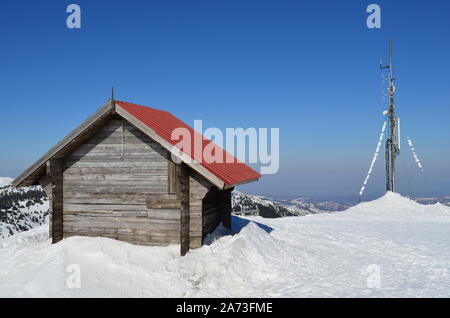 The end of winter, wooden shelter and antenna on the top of the mountin, sunny day and melting snow - Stock Photo