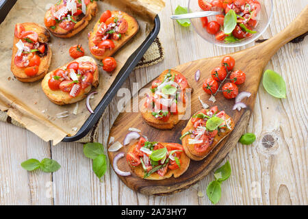 Warm Italian bruschetta: Crispy baked Italian ciabatta bread with cherry tomatoes, basil and parmesan cheese, served as an appetizer - Stock Photo