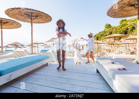 Happy family dancing on the beach lounge. Mother and two daughter have fun on summer vacation. - Stock Photo