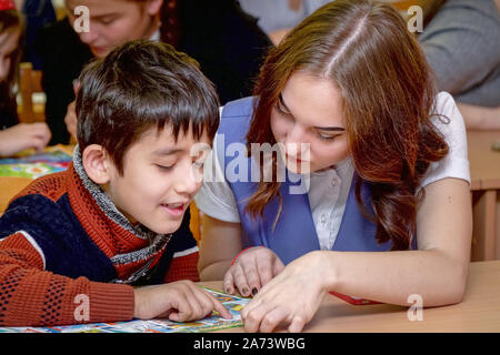 Chapaevsk, Samara region, Russia - October 15, 2019: Elementary school in Chapaevsk. Schoolboy at a desk with a woman teacher. The teacher is engaged - Stock Photo