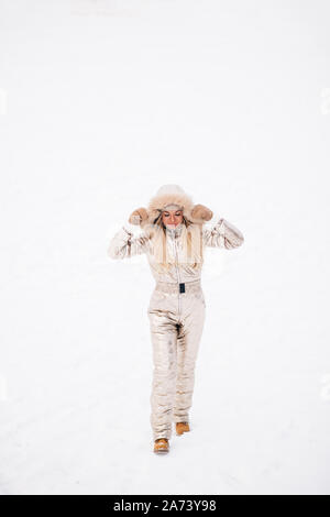 Full-length portrait of fashionable blonde caucasian woman walking in snow in cold winter day, smiling, enjoying time in ski resort. Winter holidays, - Stock Photo