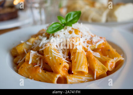 Food photography of an italian pasta dish with a tomato cream sauce and parmesan cheese - Stock Photo