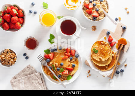 pancakes with blueberry strawberry honey and nuts for breakfast - Stock Photo