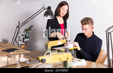 Young female architect helping male colleague making elements on scroll saw for architectural model in design bureau - Stock Photo