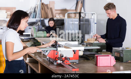 Young architects working on machine tools, creating new architectural model in design bureau - Stock Photo