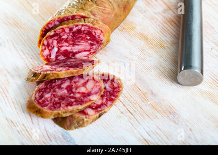 Appetizing salchichon sausage on wooden table - Stock Photo