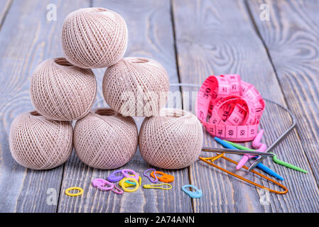 Balls of yarn, knitting needles, measuring tape and paper clips on wooden background. - Stock Photo