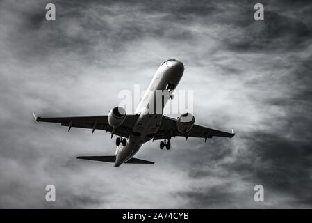 Airplane landing in front of dramatic sky in black and white | usage worldwide