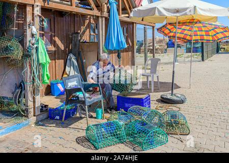 09.16.2019. Algarve, Portugal. Local fisherman repairing octopus traps, Santa Luzia, East Algarve - Stock Photo