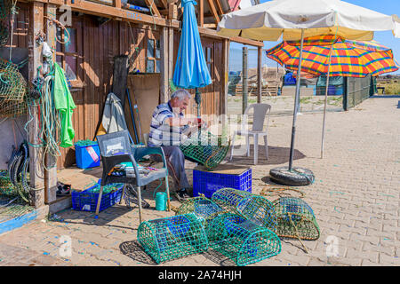 09.16.2019. Algarve, Portugal. Local fisherman repairing octopus traps, Santa Luzia, East Algarve - Stock Photo