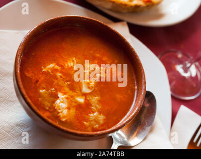 Typical dish from Castilla. Spicy garlic soup (Sopa de ajo) with Spanish smoked paprika, bread and egg - Stock Photo