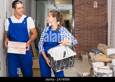Female and male workers holding bricks during decorating work in room - Stock Photo