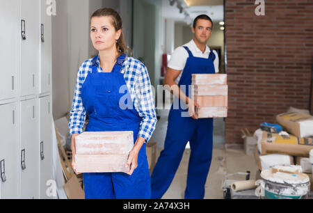 Happy female and male workers holding bricks during decorating work in room - Stock Photo