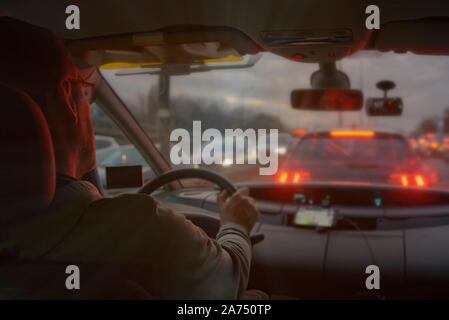 Driving a car in the city at night in traffic jams. the concept of a difficult return home - Stock Photo
