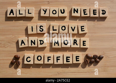 All You Need Is Love And More Coffee-. Words in 3d wooden alphabet letters with coffee beans on a bamboo wood background