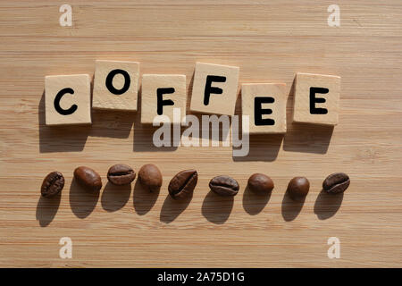 Coffee.  Word in 3d wooden alphabet letters with coffee beans on a bamboo wood background - Stock Photo