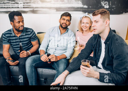 Group of diverse joyful friends having fun at home party, cheerfully laughing, enjoying drinks sitting on sofa in living room. People, leisure and fri - Stock Photo