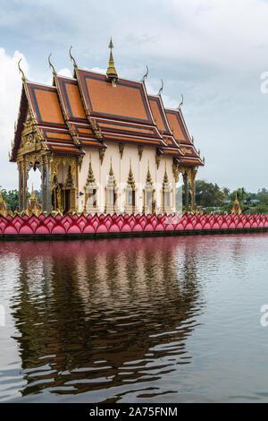 Ko Samui Island, Thailand - March 18, 2019: Wat Laem Suwannaram Chinese Buddhist Temple. Wat Plai Laem shrine on its platform upon pink lotus reflecte - Stock Photo