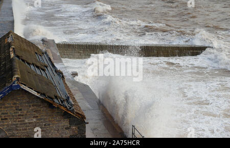 Rough sea at Dawlish, and the storm damaged roof of a building beside the railway.. - Stock Photo