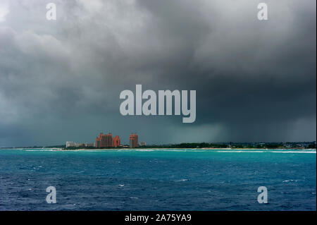 Views of Paradise Island under stormy skies where Atlantis Resort can be seen from a cruise ship entering Nassau's Harbor. - Stock Photo
