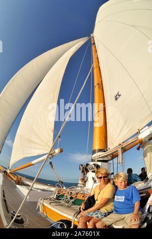 Passengers enjoying cruise on Schooner America 2.0 plying turquoise waters during sunset sail off Key West, Florida Keys, Florida, USA - Stock Photo