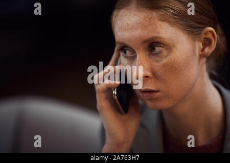 Young red haired businesswoman looking very seriously she talking on the mobile phone - Stock Photo