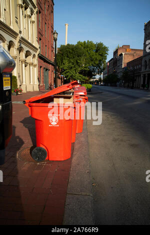 orange commercial recycling bins left on the sidewalk early morning downtown main st louisville kentucky USA - Stock Photo
