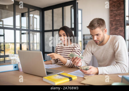 Husband counting money while filling tax declaration - Stock Photo