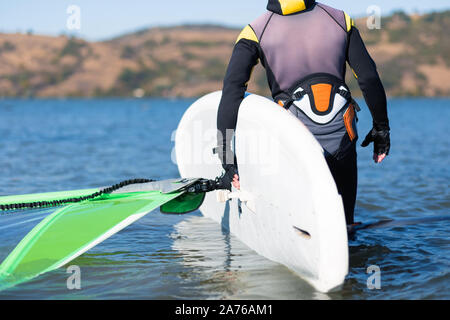 Close up of windsurfer carrying surfboard with sail in shallow water. - Stock Photo