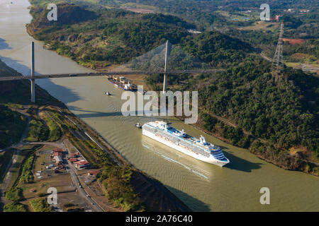 Amazing aerial image of a luxury cruise ship going under the Centennial Bridge in Panama Canal - Stock Photo