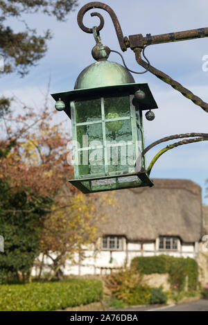 vintage green glass street lamp with a thatched cottage in the background - Stock Photo