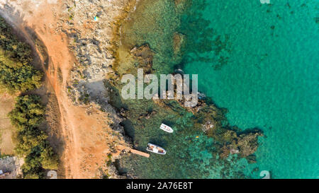 Aerial view of rocky beach on turquoise Adriatic Sea with boats moored near shore, Puglia coastline, southern region of Italy. - Stock Photo
