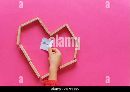 Heart shape made of wooden pegs with child hand placing post it paper with Family written on it inside the heart. Over pink background. - Stock Photo