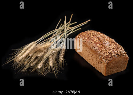 Tasty dark bread with sunflower and dry ears of wheat. Ingredients for making sandwiches on a dark table. Black background. - Stock Photo
