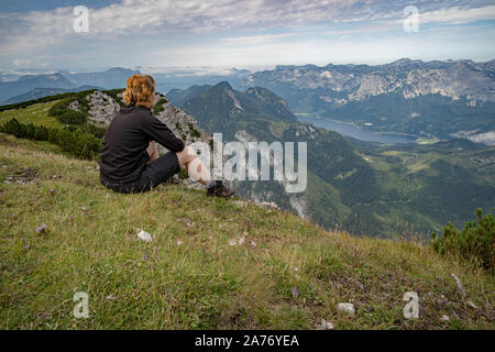 A young woman relaxes with a view of a mountain lake after a busy hike - Stock Photo