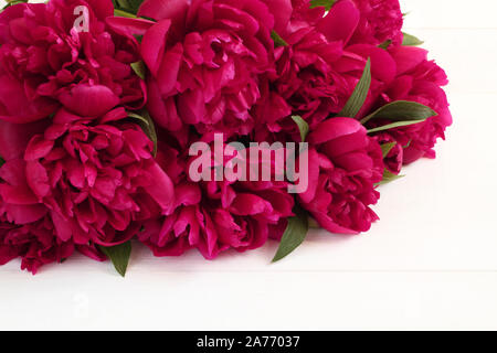 Bouquet of magenta peonies lying on white wooden table. Closeup - Stock Photo