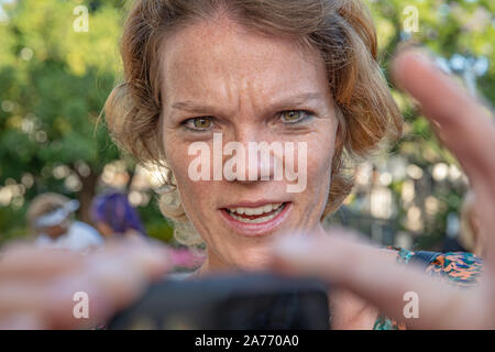 A girl shoots a video of the sea on a small camera. A woman in a hat shoots a video on an action camera as a keepsake. - Stock Photo