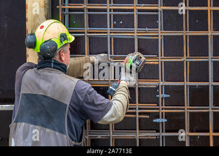 Construction worker bending - wiring concrete steel bars with a machine, outdoors in Nuuk. - Stock Photo