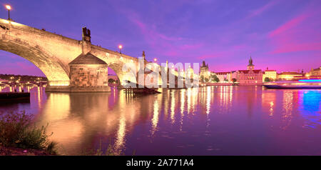 Prague at night, panoramic image. Illuminated Charles bridge, Bridge Tower and old buildings on the riverside under purple sky with golden reflections - Stock Photo