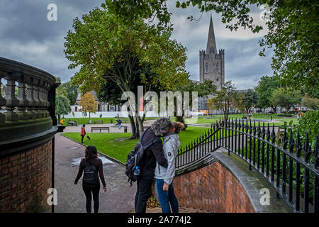 Couple Kissing, St Patrick's Cathedral from St Patrick's Park, Dublin, Ireland - Stock Photo