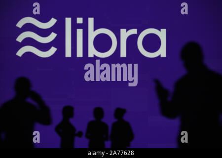 The Libra cryptocurrency logo is seen on an LED screen in the background while a silhouetted person uses a smartphone (Editorial use only) - Stock Photo