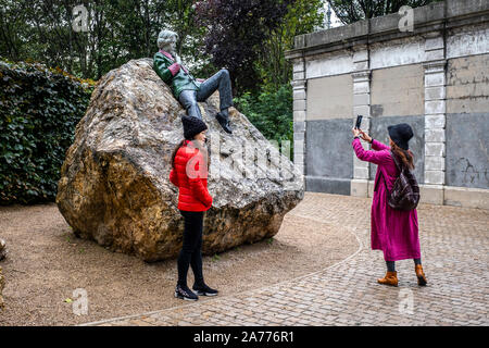 Tourists and statue of Irish writer Oscar Wilde by Danny Osbourne in Merrion Square, Dublin, Ireland - Stock Photo