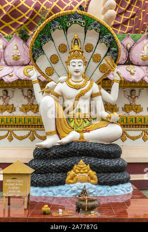Ko Samui Island, Thailand - March 18, 2019: Wat Laem Suwannaram Chinese Buddhist Temple. Closeup of Lord Vishnu statue sitting on coil of snake and mu - Stock Photo