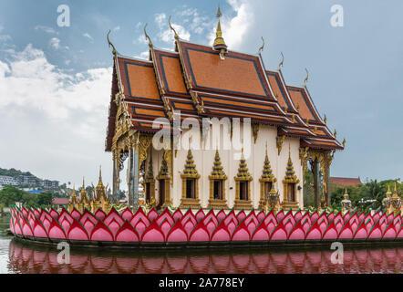Ko Samui Island, Thailand - March 18, 2019: Wat Laem Suwannaram Chinese Buddhist Temple. Closeup of Wat Plai Laem shrine on its platform upon pink lot - Stock Photo